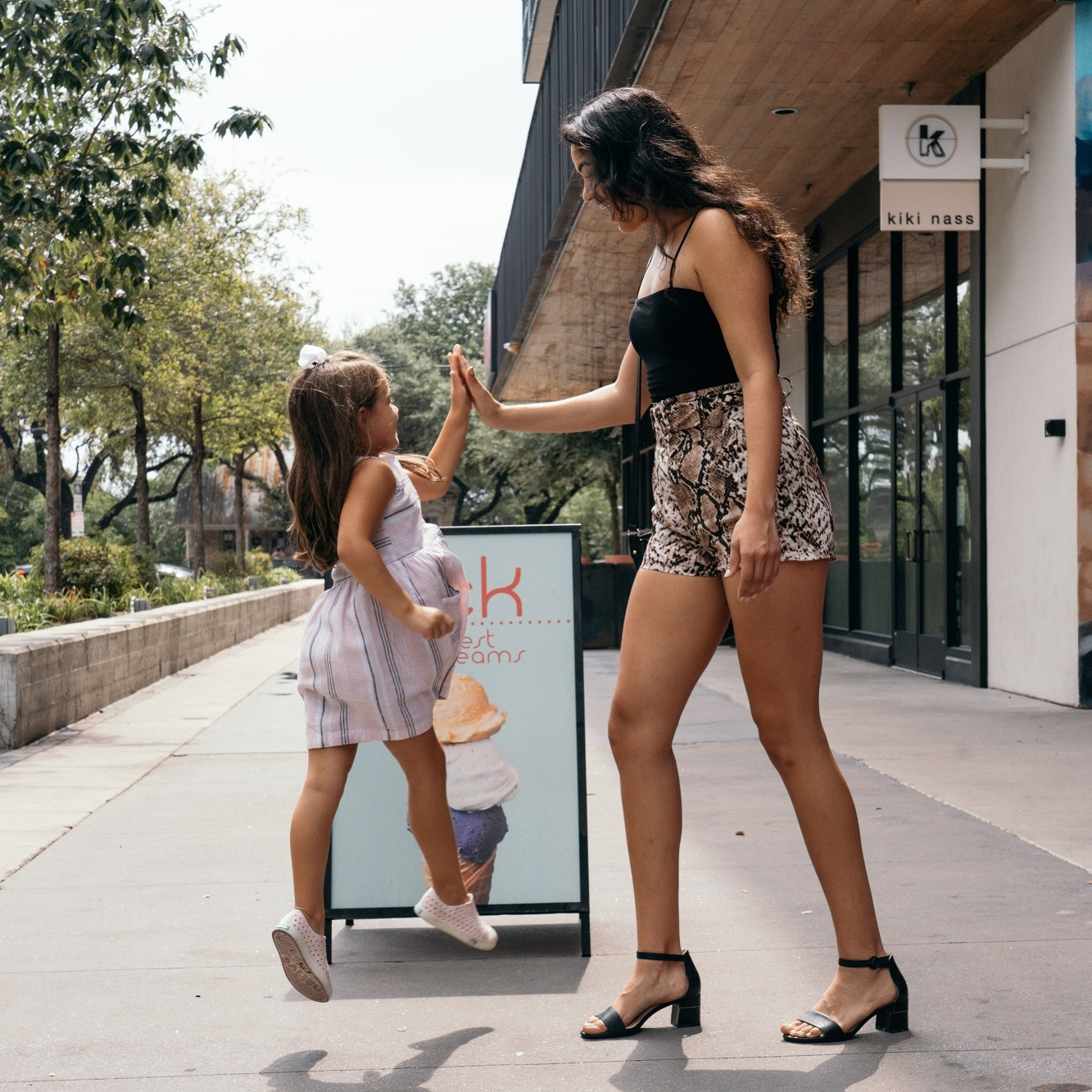 Mom and daughter giving high five outside at plaza